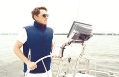 站立在游艇的一个方向盘的英俊,年轻人 Tra 免版税库存图片