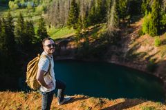站立在湖上的峭壁的人有反射在它的天空的 免版税库存图片