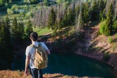 站立在湖上的峭壁的人有反射在它的天空的 库存图片