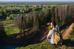 站立在湖上的峭壁的人有反射在它的天空的 免版税库存照片