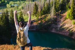 站立在湖上的峭壁的人有反射在它的天空的 库存照片