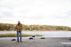 站立在湖和森林附近的人 免版税库存图片