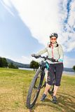 站立在湖岸的女性旅游骑自行车者画象  免版税库存图片