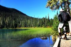 站立在湖旁边的旅行家 库存照片