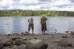 站立在湖边钓鱼旁边的可爱的更旧的夫妇 库存图片