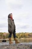 站立在湖附近的成熟妇女 免版税图库摄影