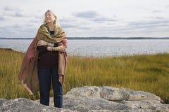 站立在湖附近的资深妇女 免版税库存照片