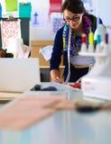 站立在演播室的美丽的时装设计师 免版税图库摄影