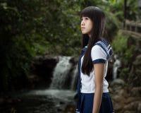 站立在瀑布前面的亚裔女小学生 免版税库存照片