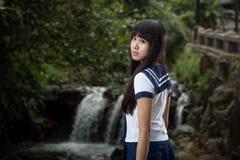 站立在瀑布前面的亚裔女小学生 免版税库存图片