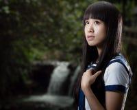 站立在瀑布前面的亚裔女小学生 免版税图库摄影