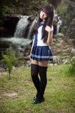 站立在瀑布前面的亚裔女小学生 图库摄影