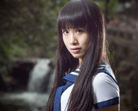 站立在瀑布前面的亚裔女小学生 库存照片