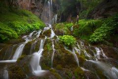 站立在瀑布旁边的妇女在老保守早晨 图库摄影