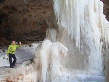 站立在瀑布旁边的微笑的妇女 免版税库存照片