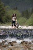 站立在瀑布的妇女和她的狗 免版税库存照片