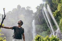 站立在瀑布附近的年轻人在森林里 免版税图库摄影