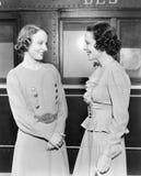 站立在火车和微笑前面的两名妇女(所有人被描述不更长生存,并且庄园不存在 供应商战争 免版税库存图片