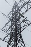 站立在灰色天空背景的高压传输塔的特写镜头大气照片在飞雪以后 图库摄影