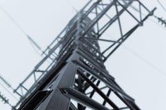 站立在灰色天空背景的高压传输塔的特写镜头大气照片在飞雪以后 免版税库存图片