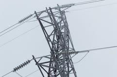 站立在灰色天空背景的高压传输塔的特写镜头大气照片在飞雪以后 库存照片