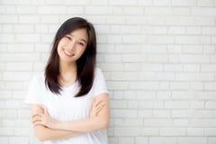 站立在灰色水泥纹理难看的东西墙壁砖背景的美好的年轻亚洲妇女幸福画象  免版税库存图片
