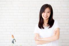 站立在灰色水泥纹理难看的东西墙壁砖背景的美好的年轻亚洲妇女幸福画象  库存照片