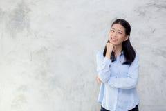 站立在灰色水泥纹理难看的东西墙壁背景的美好的年轻亚洲妇女幸福画象  免版税库存照片