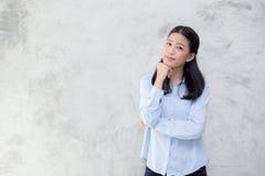 站立在灰色水泥纹理难看的东西墙壁背景的美好的年轻亚洲妇女幸福画象  库存图片