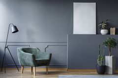 站立在灰色的一盏绿色扶手椅子和黑灯的真正的照片 免版税库存照片