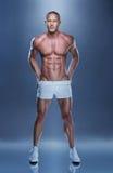站立在灰色背景的赤裸上身的肌肉人 库存照片