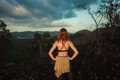 站立在热带气候的被烧焦的小山的妇女 免版税库存照片