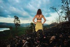 站立在热带气候的被烧焦的小山的妇女 库存照片