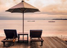 站立在热带海滩的一个木平台的两把sunbeds和伞在日落 镇静休息的概念 库存照片