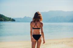 站立在热带海滩的亭亭玉立的少妇 免版税库存图片