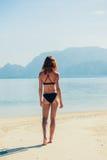 站立在热带海滩的亭亭玉立的少妇 图库摄影
