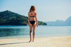站立在热带海滩的亭亭玉立的少妇 免版税图库摄影