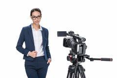 站立在照相机前面的可爱的女性新闻广播员, 免版税库存图片