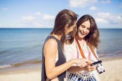 站立在照相机的海滩观看的照片的愉快的妇女 免版税图库摄影