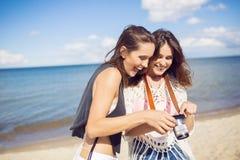 站立在照相机laug的海滩观看的照片的美丽的妇女 库存图片