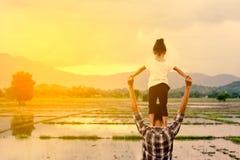 站立在父亲` s肩膀的后面观点的亚裔小女孩 免版税图库摄影