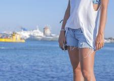 站立在牛仔裤的一个船坞的少妇的美好的腿短缺 库存照片