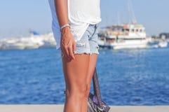 站立在牛仔裤的一个船坞的少妇的美好的腿短缺 免版税图库摄影