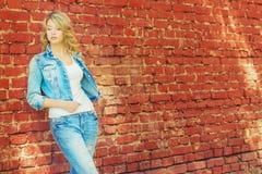 站立在牛仔布夹克和裤子的一个砖墙附近的美丽的性感的白肤金发的妇女 免版税库存图片