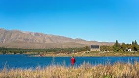 站立在特卡波湖岸的游人拍摄好牧羊人,新西兰的教会 库存照片