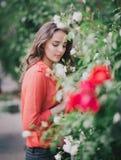站立在玫瑰中的一条红色裙子的美丽的少妇 免版税库存图片