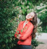 站立在玫瑰中的一条红色裙子的美丽的少妇 图库摄影
