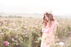 站立在玫瑰园里的微笑的十几岁的女孩 库存图片