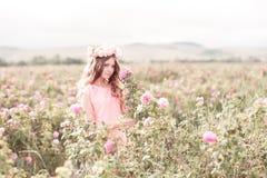 站立在玫瑰园里的青少年的女孩 库存照片