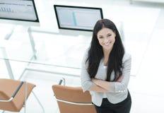 站立在现代工作场所附近的年轻女商人 免版税库存照片